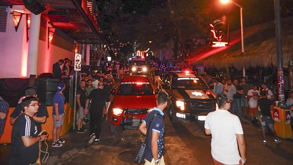 People remain in the street outside the Blue Parrot nightclub as firefighters and police agents patrol the area in Playa del Carmen, Quintana Ro state, Mexico where 5 people were killed, three of them foreigners, during a music festival on January 16, 2017.  A shooting erupted at an electronic music festival in the Mexican resort of Playa del Carmen early Monday, leaving at least five people dead and sparking a stampede, the mayor said. Fifteen people were injured, some in the stampede, after at least one shooter opened fire before dawn at the Blue Parrot nightclub during the BPM festival. / AFP PHOTO / VICTOR VARGAS / MAXIMUM QUALITY AVAILABLE