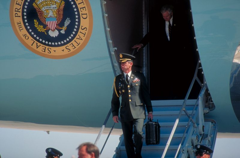 Dep. NSC Adviser Bob Gates de- planing, w. football carrier (mil. aide w. briefcase-carried nuclear missile launch code), in fore, (w. campaigning Pres. Bush) in CA.  (Photo by Diana Walker//Time Life Pictures/Getty Images)