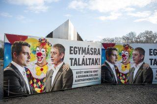 """Budapest, 2016. december 7. A Civil Összefogás Fórum (CÖF) újabb plakátja a budapesti Ötvenhatosok terén 2016. december 7-én. A kép Vona Gábor Jobbik-elnököt és Gyurcsány Ferenc DK-elnököt öleli át a korábbi plakátkampányból ismert bohóc, a felirat pedig azt hirdeti: """"Egymásra találtak! Együtt mondtak nemet a bevándorlásellenes alkotmánymódosításra"""". MTI Fotó: Marjai János"""
