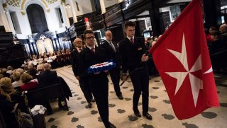 LONDON, ENGLAND - DECEMBER 09: Order of Malta Cadets carry the Order's flag and a wreath during an Anglo-Polish Carol Service at the St Clement Danes Church on December 9, 2016 in London, England. The annual Carol of the Bells service is held tonight in aid of the Polish Knights of Malta's Centre for Disabled Children in Katowice, Poland. (Photo by Jack Taylor/Getty Images)