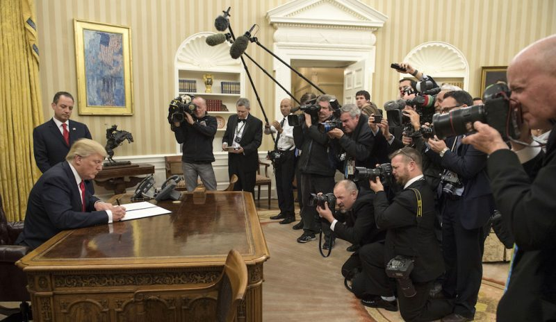 """U.S. President Donald Trump signs an executive order commanding federal agencies to try to waive or delay requirements of former President Barack Obama's health-care law, the Affordable Care Act (ACA), in the Oval Office of the White House in Washington, D.C., U.S., on Friday, Jan. 20, 2017. The order declares that Trump's administration will seek the """"prompt repeal"""" of the law, and that the government should prepare to """"afford the states more flexibility and control to create a more free and open healthcare market."""" Photographer: Kevin Dietsch/Pool via Bloomberg"""