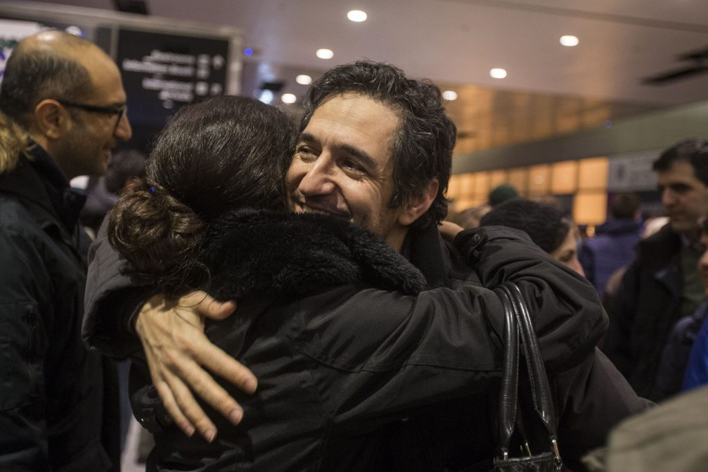 BOSTON, MA - JANUARY 28: Mazdak Tootkaboni is embraced during a demonstration against the new ban on immigration issued by President Donald Trump at Logan International Airport on January 28, 2017 in Boston, Massachusetts. Tootkaboni is a U.S. green card holder from Iran and a professor at the University of Massachusetts at Dartmouth, but he was still separated from other passengers and questioned as a result of the new immigration ban issued by President Donald Trump. President Trump signed an executive order that halted refugees and residents from predominantly Muslim countries from entering the United States. (Photo by Scott Eisen/Getty Images)