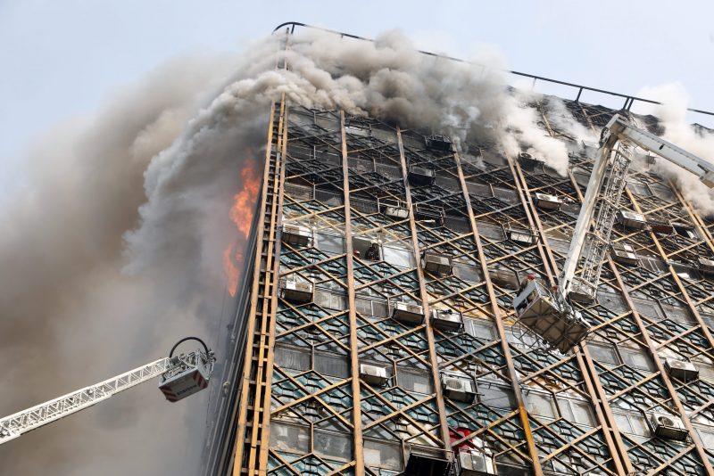 Teherán, 2017. január 19. Daruk emelõkosarában érkeznek tûzoltók a lángokban álló Plasco toronyházhoz Teheránban 2017. január 19-én, miután egyelõre ismeretlen okból tûz ütött ki az épületben, amelynek felsõ szintjei beomlottak. Az iráni állami televízió szerint a felhõkarcolóban rekedt emberek és a tûzoltók közül többen életüket vesztették, legkevesebb 38-an megsérültek. (MTI/EPA/Abedin Taherkenareh)