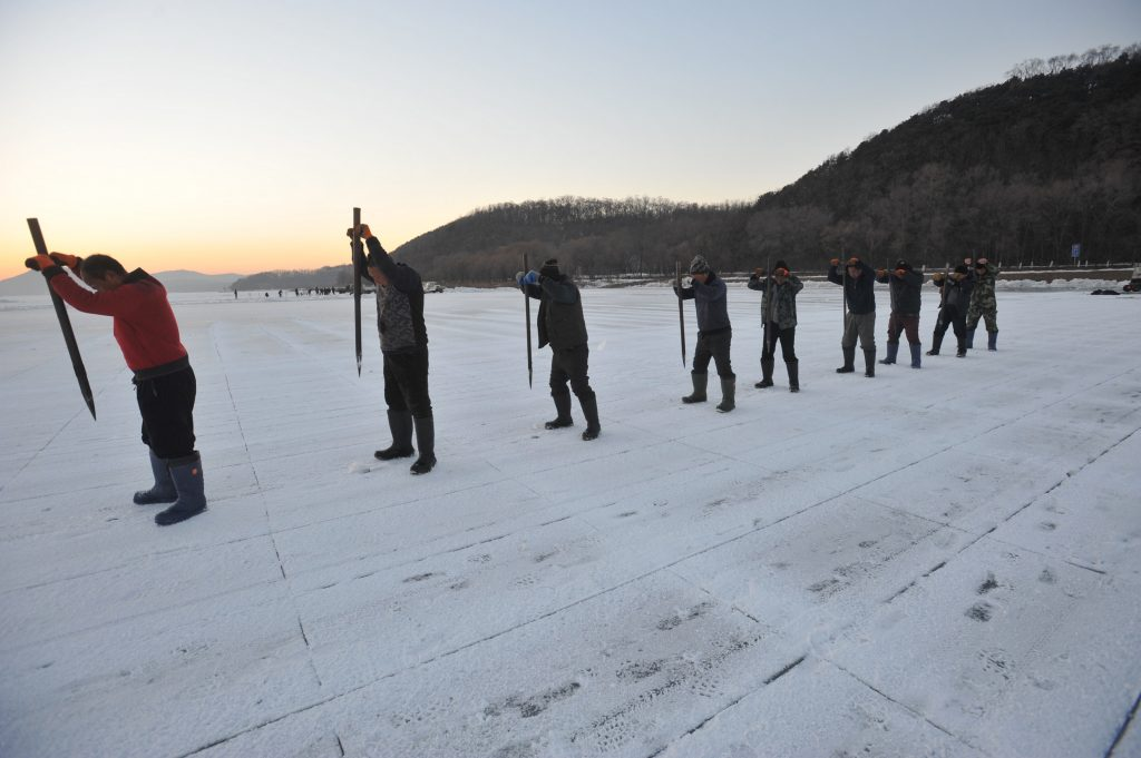 Chinese workers prepare to chisel the frozen Xiuhu Lake in Qipan Mountain to collect ice blocks in Shenyang city, northeast China's Liaoning province, 4 January 2017.  Chinese workers collected ice blocks from the frozen Xiuhu Lake in Qipan Mountain in Shenyang city, northeast China's Liaoning province. The ice blocks collected in Liaoning's coastal areas are used for preserving sea food, a practice that dates back 100 years. About 700 ice-collecting devices can create 700,000 ice blocks a day, generating a total output of nearly 200 million yuan ($29 million) in one month.