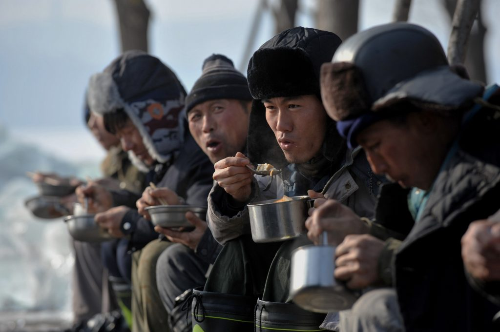 Chinese ice block collectors eat lunch on the frozen Xiuhu Lake in Qipan Mountain in Shenyang city, northeast China's Liaoning province, 2 January 2017.  Chinese workers collected ice blocks from the frozen Xiuhu Lake in Qipan Mountain in Shenyang city, northeast China's Liaoning province. The ice blocks collected in Liaoning's coastal areas are used for preserving sea food, a practice that dates back 100 years. About 700 ice-collecting devices can create 700,000 ice blocks a day, generating a total output of nearly 200 million yuan ($29 million) in one month.