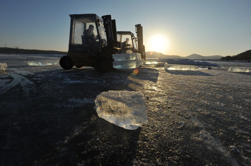 Chinese workers use ice-collecting machines to collect ice blocks on the frozen Xiuhu Lake in Qipan Mountain in Shenyang city, northeast China's Liaoning province, 2 January 2017.  Chinese workers collected ice blocks from the frozen Xiuhu Lake in Qipan Mountain in Shenyang city, northeast China's Liaoning province. The ice blocks collected in Liaoning's coastal areas are used for preserving sea food, a practice that dates back 100 years. About 700 ice-collecting devices can create 700,000 ice blocks a day, generating a total output of nearly 200 million yuan ($29 million) in one month.