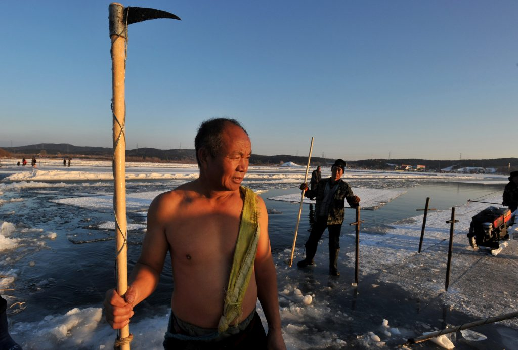 Chinese workers pose with their tools to collect ice blocks on the frozen Xiuhu Lake in Qipan Mountain in Shenyang city, northeast China's Liaoning province, 2 January 2017.  Chinese workers collected ice blocks from the frozen Xiuhu Lake in Qipan Mountain in Shenyang city, northeast China's Liaoning province. The ice blocks collected in Liaoning's coastal areas are used for preserving sea food, a practice that dates back 100 years. About 700 ice-collecting devices can create 700,000 ice blocks a day, generating a total output of nearly 200 million yuan ($29 million) in one month.