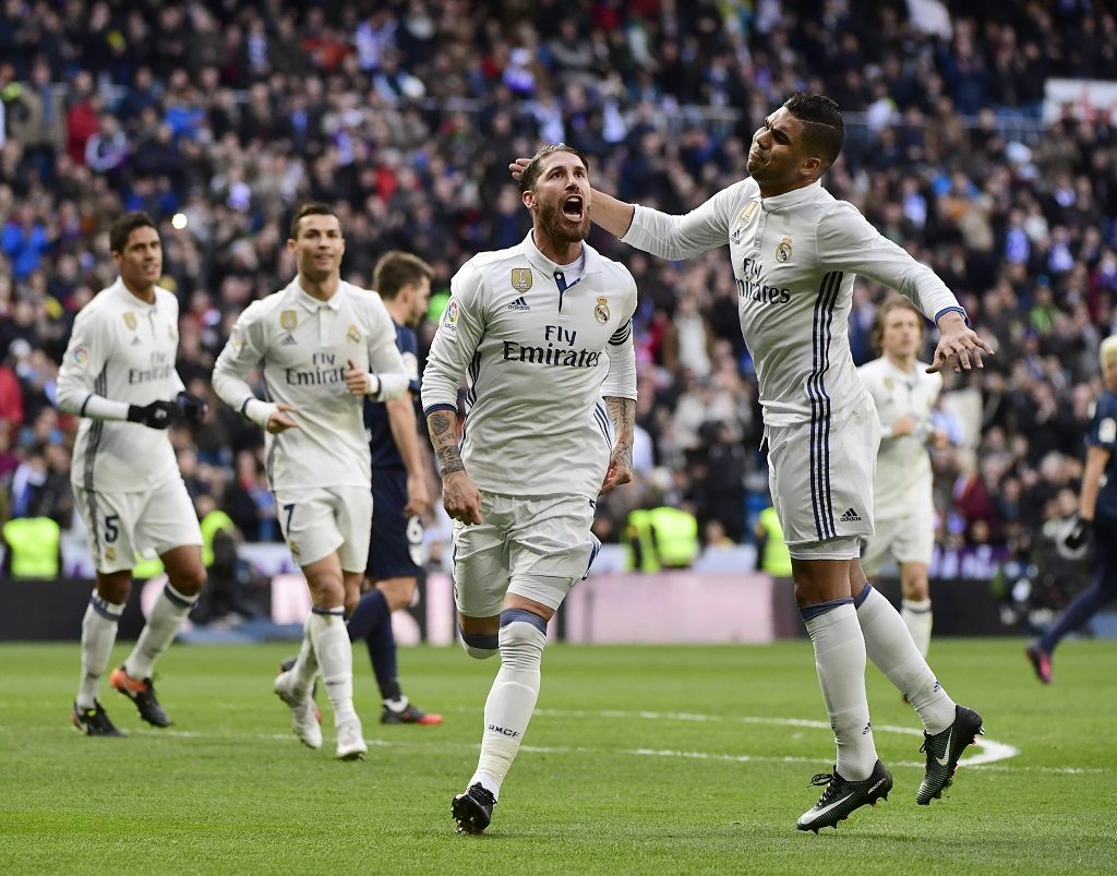 Real Madrid's defender Sergio Ramos (L) celebrates with Real Madrid's Brazilian midfielder Casemiro after scoring  during the Spanish league football match Real Madrid CF vs Malaga CF at the Santiago Bernabeu stadium in Madrid on January 21, 2017. / AFP PHOTO / PIERRE-PHILIPPE MARCOU