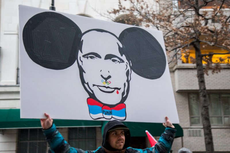 [UNVERIFIED CONTENT] A protester with an anti-Putin poster depicting Putin's face with the Olympic rings, blood and Cheburashka ears during a mass demonstration against Russian troops invading Crimea, Ukraine, taken on March 2, 2014 in front of the Russian Consulate in New York City, USA.