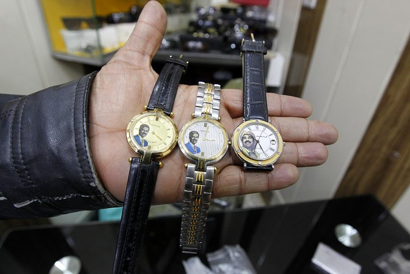 An Iraqi shopkeeper holds watches bearing portraits of late Iraqi president Saddam Hussein at his shop in the capital Baghdad on December 28, 2016. While Saddam was brutal to those who opposed him and led his country into two disastrous wars, there are those who still look back fondly on his time in power, especially in comparison to the years of devastating internal violence and ineffective governance that followed his overthrow in 2003. / AFP PHOTO / SABAH ARAR / TO GO WITH AFP STORY BY GUILLAUME DECAMME