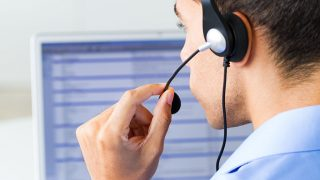 man wearing headset looking at computer monitor