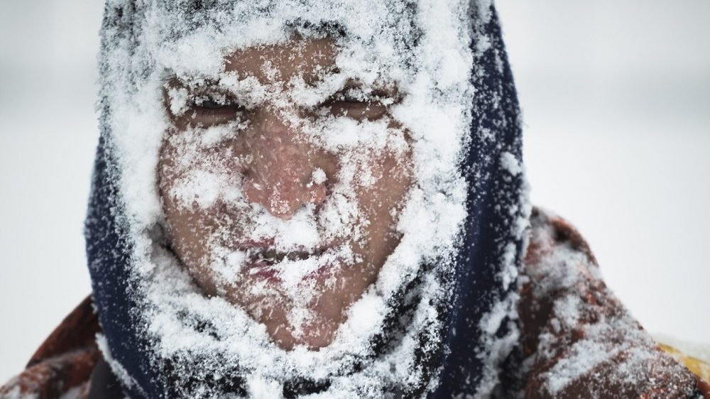 Man covered by snow in snowstorm.