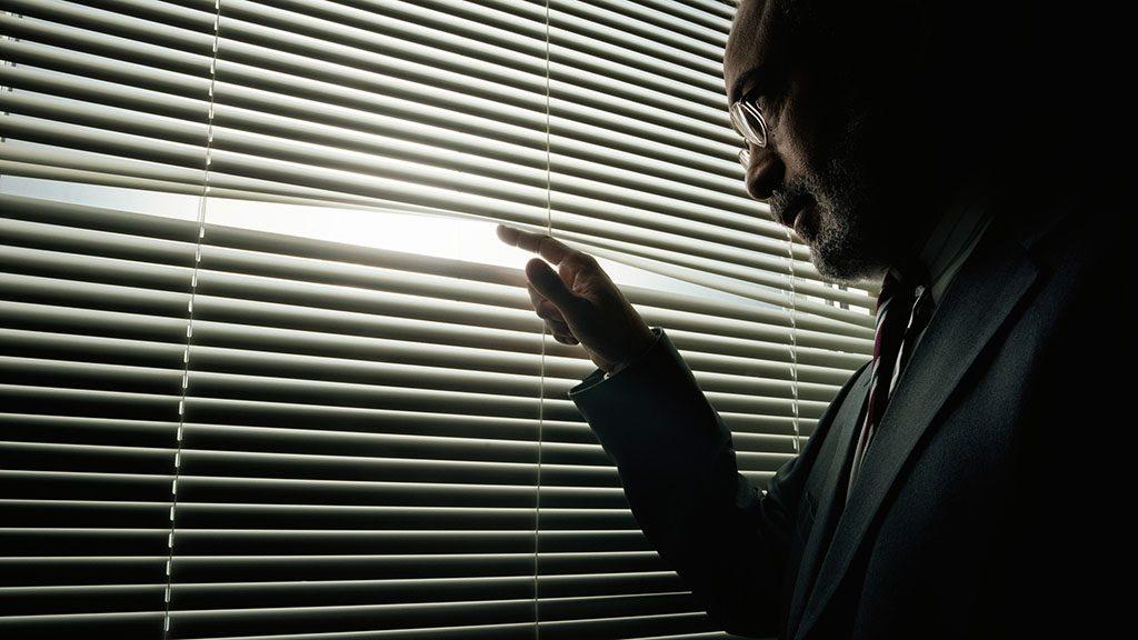Mature man peeking through window blinds