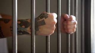Man behind prison bars.