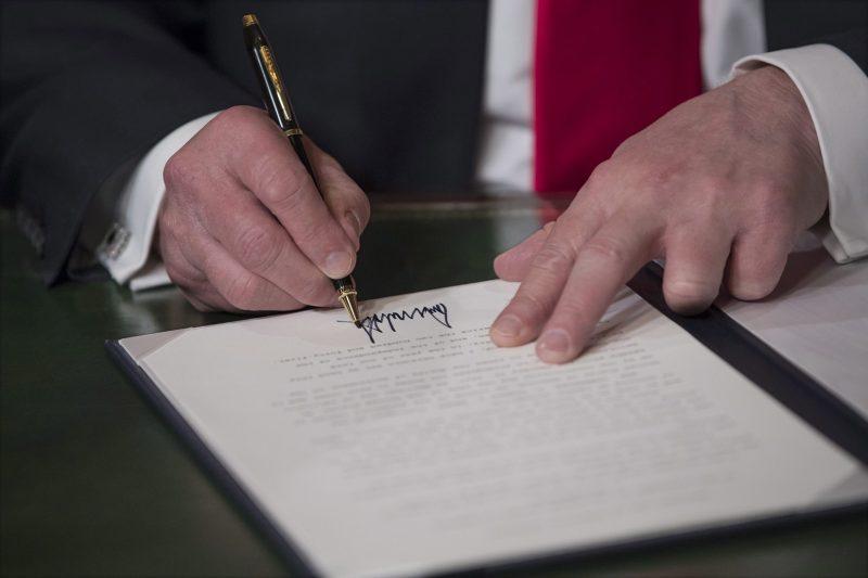 Washington, 2017. január 20. Donald Trump, az Egyesült Államok 45. elnöke kézjegyével látja el a beiktatási dokumentumokat Washingtonban 2017. január 20-án. (MTI/EPA pool/J. Scott Applewhite)