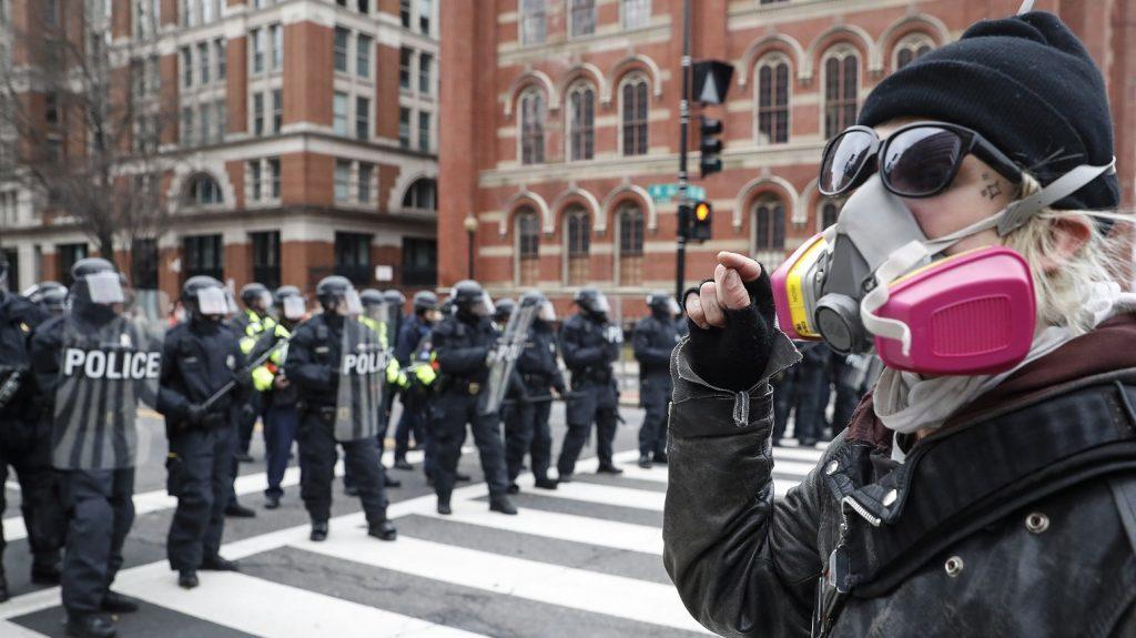 Washington, 2017. január 20. Tüntetõ néz farkasszemet rendõrökkel Donald Trump megválasztott amerikai elnök washingtoni beiktatási ünnepsége után az elnöki díszmenet útvonalán 2017. január 20-án. (MTI/AP/John Minchillo)