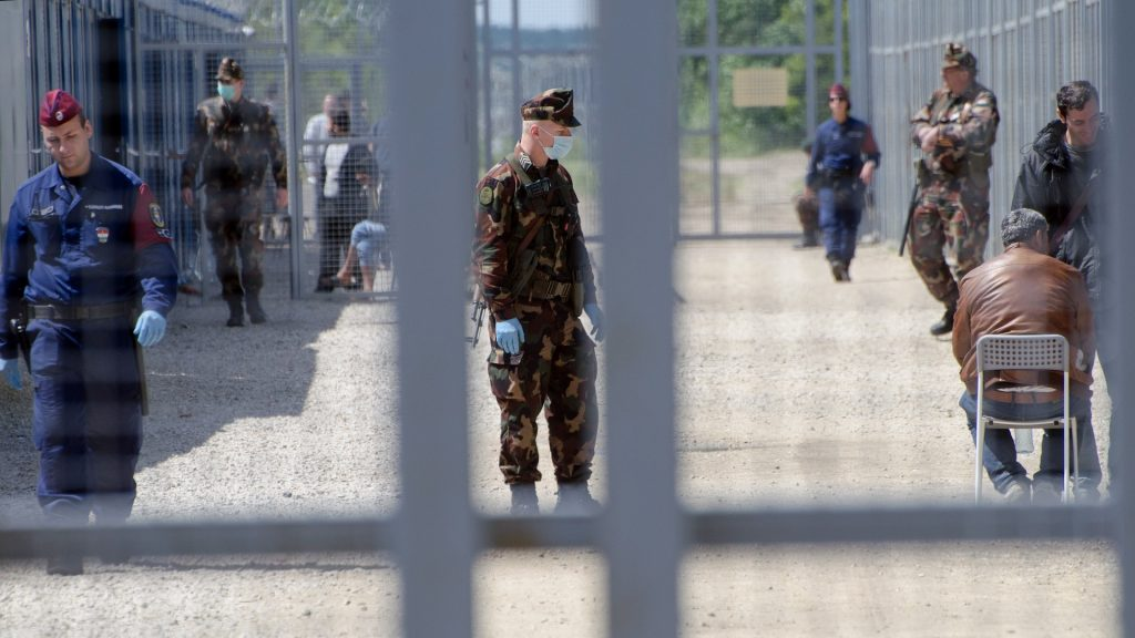 """Migrants wait in the Hungarian transit zone nearby the motorway border crossing of Röszke between Hungary and Serbia on April 26, 2016. Dozens of migrants arrive at the border every day, awaiting admittance into two caged-off Hungarian """"transit zones"""" built into the fence, one at Roszke and another at Tompa 20 kilometres (12 miles) away.  / AFP PHOTO / Csaba SEGESVARI / TO GO WITH AFP STORY by PETER MURPHY"""