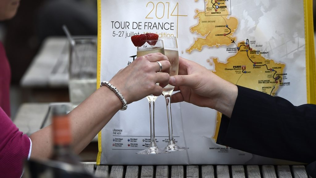 A couple toasts with Champagne beside a 2014 Tour de France bag on July 1, 2014 in Leeds, northwestern England, before the start of the 101st edition of the Tour de France cycling race. The 2014 Tour de France gets underway on July 5 in the streets of Leeds and ends on July 27 down the Champs-Elysees in Paris.   AFP PHOTO / LIONEL BONAVENTURE / AFP PHOTO / LIONEL BONAVENTURE