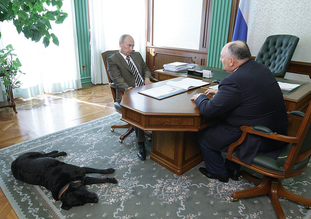 Russian Prime Minister Vladimir Putin (L) meets the owner of Akron Holding Vyacheslav Kantor (R) at an undisclosed location in Russia on July 27, 2010. Putin's pet labrador dog Koni lies on the floor nearby.  AFP PHOTO / RIA NOVOSTI / POOL / ALEXEY DRUZHININ / AFP PHOTO / RIA NOVOSTI / ALEXEY DRUZHININ