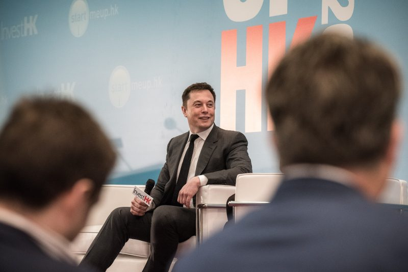 Elon Musk (C), the co-founder of luxury all-electric US car maker Tesla, speaks at the StartmeupHK Venture Forum in Hong Kong on January 26, 2016. Plunging oil prices will force electric car makers to design futuristic vehicles to entice buyers if the industry is to ride out current challenges, Musk said on January 26.    AFP PHOTO / Philippe Lopez / AFP PHOTO / PHILIPPE LOPEZ