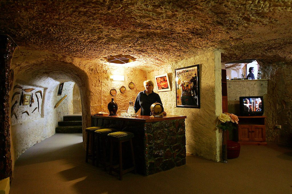 Judy McLean displays the subterranean bar and lounge of Faye's underground house in the opal mining town of Coober Pedy, 05 July 2005, located 840 kms north of Adelaide. Living in one of the world's most inhospitable regions -- a tree-less, stony desert where temperatures can climb to 50 degrees Celcius in the day and fall to zero at night -- half of Coober Pedy's 3,500 residents have dug their homes into the chalky clay rock to escape the harsh conditions.  AFP PHOTO/Torsten BLACKWOOD / AFP PHOTO / TORSTEN BLACKWOOD