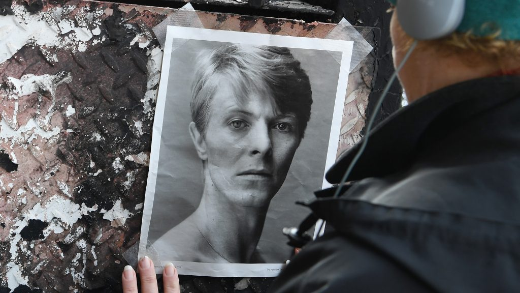 A woman tapes a David Bowie picture on a wall outside of his SoHo apartment building on the first anniversary of Bowie's death on January 10, 2017 in New York City. / AFP PHOTO / ANGELA WEISS