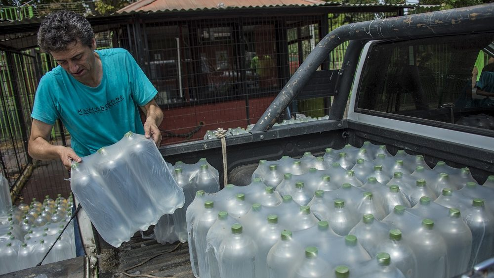 People get water during a drinking water supply cut in Santiago, on February 26, 2017. More than 1.4 million homes in Santiago were affected Sunday by a water cut from heavy rains in three regions of central Chile that left four dead and seven missing, authorities said. / AFP PHOTO / MARTIN BERNETTI