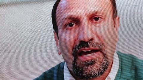 """Iranian filmmaker Asghar Farhadi speaks in a recorded video message during the public screening for the film 'The Salesman' in Trafalgar Square in central London on February 26, 2017. Thousands of film buffs gather in London's Trafalgar Square Sunday for a screening of """"The Salesman"""" by Iranian director Asghar Farhadi, who is boycotting the Oscars over US President Donald Trump's policies. / AFP PHOTO / Daniel LEAL-OLIVAS"""