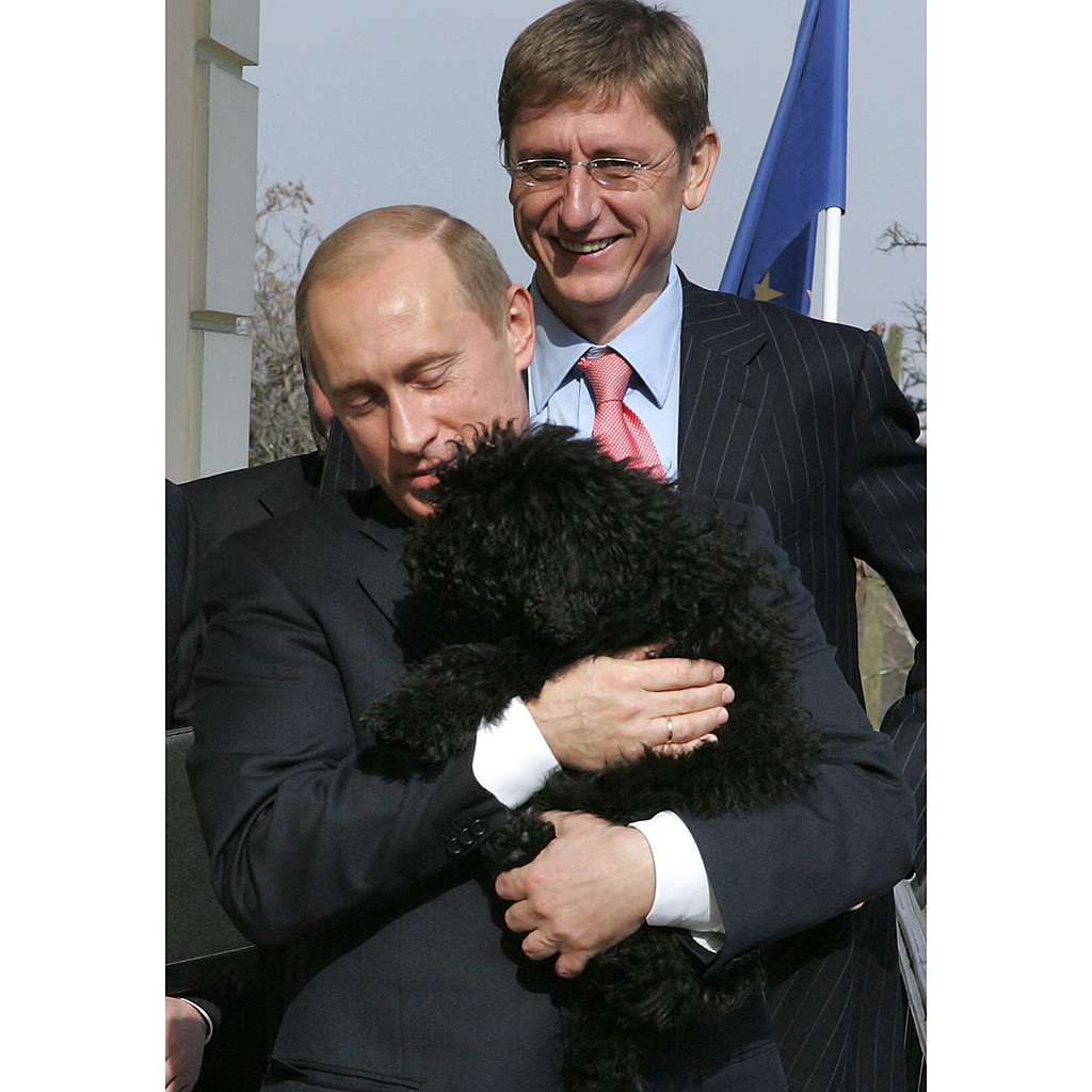Russian President Vladimir Putin hugs a Hungarian 'Puli' dog owned by Hungarian Prime Minister Ferenc Gyurcsany (background)) and his wife Klara Dobrev (out of camera range) as they stand on the balcony of the Prime Minister residence in Budapest, 01 March 2006. Putin is on a two-day official visit aimed at boosting cooperation between both countries. AFP PHOTO POOL / PRIME MINISTER OFFICE / MIKLOS DER / AFP PHOTO / POOL / MIKLOS DER