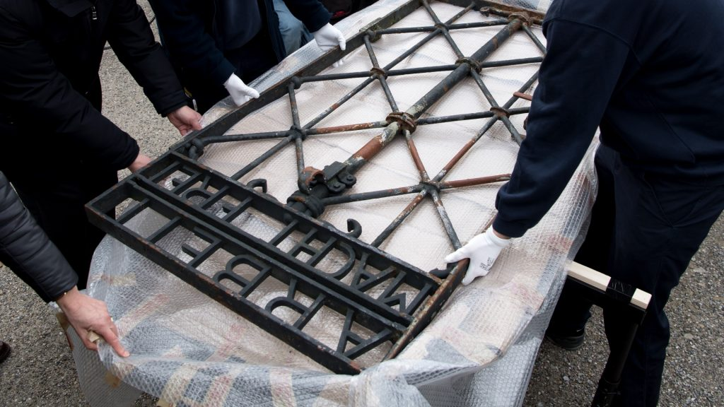 Two freight forwarders transport the historic gate of the memorial site of the former concentration camp Dachau back to its original site in Dachau, Germany, 22 February 2017. The 100 kilogram gate made of wrought iron was stolen in 2014 and reappeared in November 2016 near the city of Bergen in Norway. The theft has yet to be clarified. Photo: Sven Hoppe/dpa