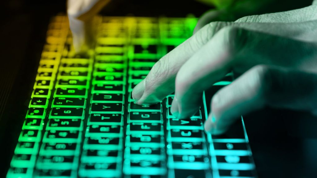 hands typing on keyboard in green light with motion blur,Concept for cybercrime hack cloud security