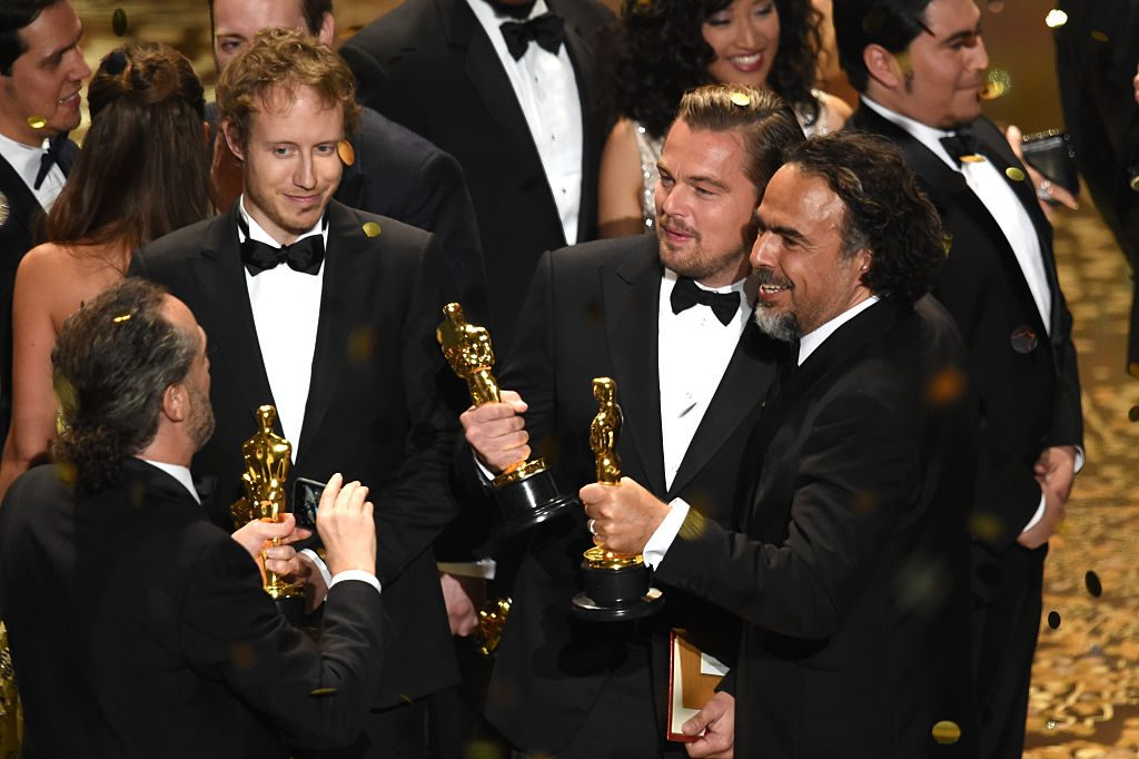HOLLYWOOD, CA - FEBRUARY 28:  Director Laszlo Nemes (2nd L), winner of Best Foreign Language Film for 'Son of Saul,' looks on as cinematographer Emmanuel Lubezki (L), winner of Best Cinematography for 'The Revenant,' takes a photo of actor Leonardo DiCaprio (2nd R), winner of Best Actor for 'The Revenant,' and director Alejandro Gonzalez Inarritu (R), winner of Best Director for 'The Revenant,' onstage during the 88th Annual Academy Awards at the Dolby Theatre on February 28, 2016 in Hollywood, California.  (Photo by Kevin Winter/Getty Images)