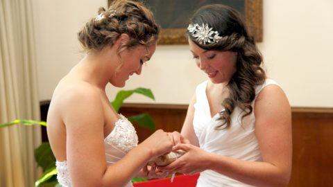 two brides getting married exchange rings in city hall