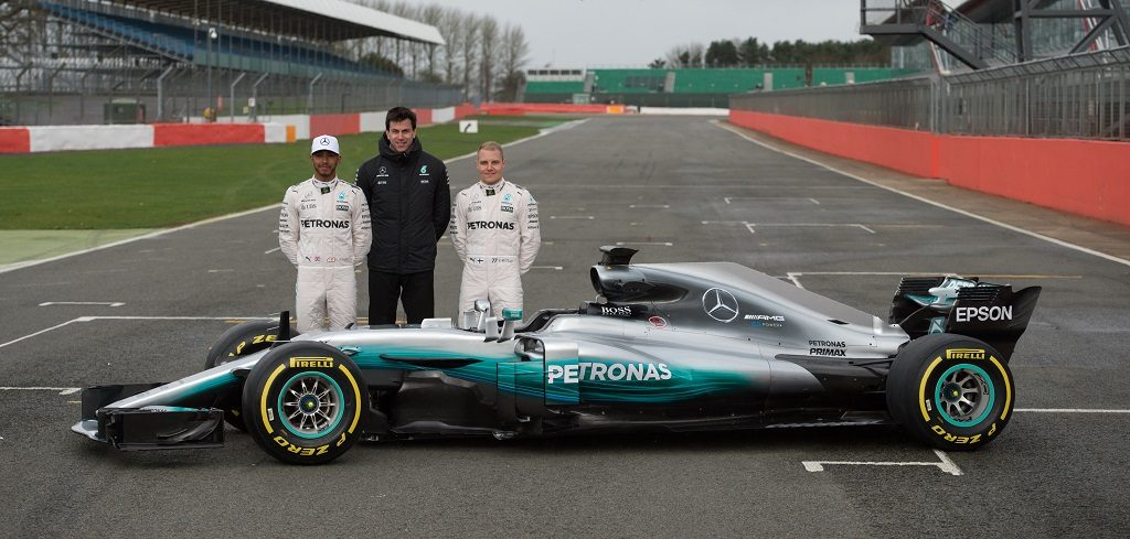 Mercedes AMG Petronas Formula One drivers Britain's Lewis Hamilton (L) and Finland's Valtteri Bottas (R) pose with Mercedes head Austria's Toto Wolff by the new 2017 season Mercedes W08 EQ Power+ Formula One car at its launch event at Silverstone motor racing circuit near Towcester, central England on February 23, 2017.  / AFP PHOTO / OLI SCARFF
