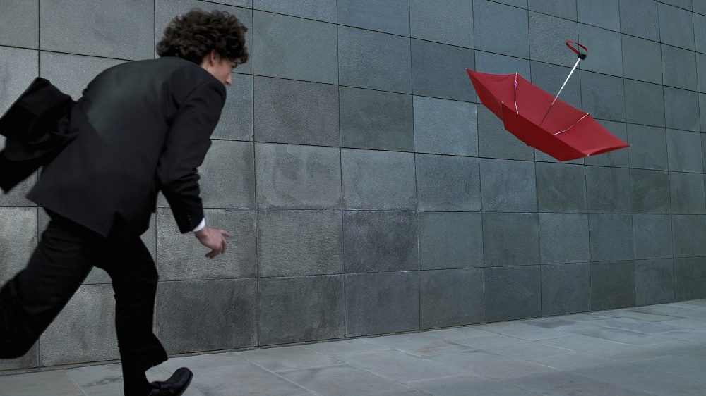 Young businessman chasing umbrella blowing in wind, rear view