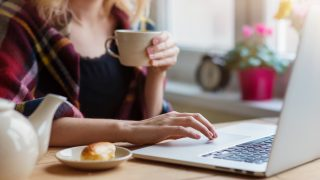 Beautiful woman relaxing at home with notebook and cup of  coffee