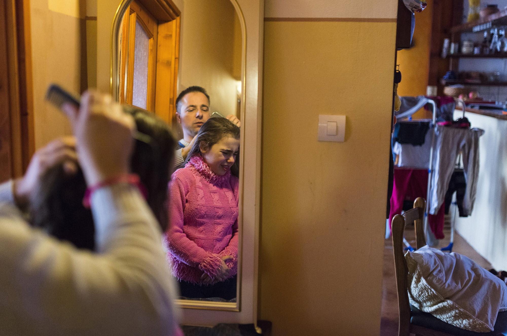 Nyíregyháza, 2017. március 30.Farkas Árpád reggel megfésüli autizmus spektrumzavarral élő lánya, Farkas Laura haját nyíregyházi otthonukban 2017. március 8-án. Az állandó felügyeletet igénylő gyermek nevelésének nehézségei miatt a család felbomlott, a szülők elváltak. A két gyermekét egyedül nevelő Farkas Árpád korábban jól működő vállalkozásaira nem tudott elég időt fordítani, így az egykor jó körülmények között élő család anyagi helyzete megváltozott. A férfi alapító elnöke az autista gyerekek szülői szervezetének, a 2014 tavaszán bejegyzett Most Élsz Egyesületnek, amely folyamatosan keresi a gyógyítás újabb és újabb lehetőségeit.MTI Fotó: Balázs Attila