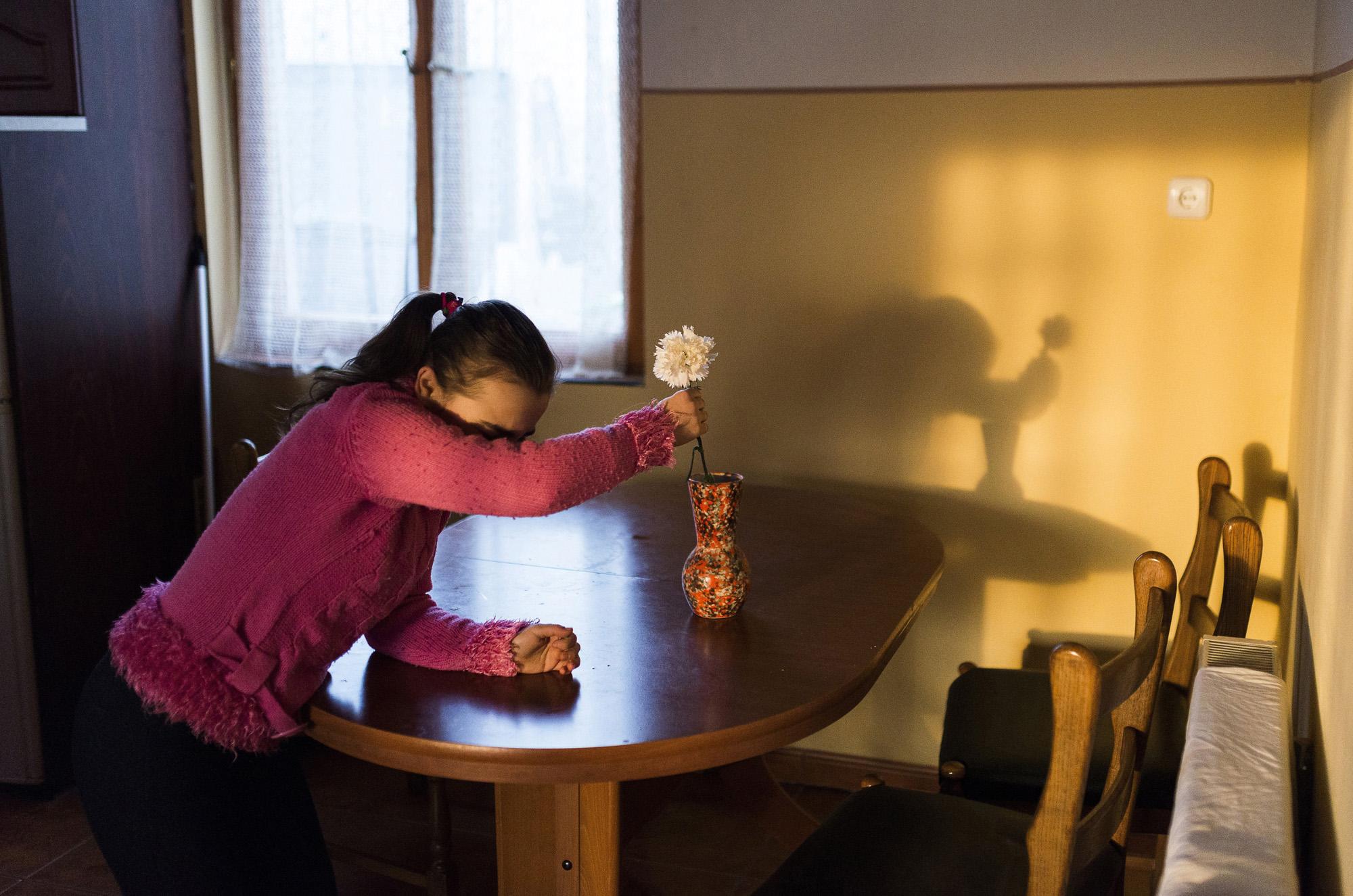 Nyíregyháza, 2017. március 30.Az autizmus spektrumzavarral élő Farkas Laura vázába teszi az édesapjától kapott virágot nyíregyházi otthonukban 2017. március 8-án. Az állandó felügyeletet igénylő gyermek nevelésének nehézségei miatt a család felbomlott, a szülők elváltak. A két gyermekét egyedül nevelő Farkas Árpád korábban jól működő vállalkozásaira nem tudott elég időt fordítani, így az egykor jó körülmények között élő család anyagi helyzete megváltozott. A férfi alapító elnöke az autista gyerekek szülői szervezetének, a 2014 tavaszán bejegyzett Most Élsz Egyesületnek, amely folyamatosan keresi a gyógyítás újabb és újabb lehetőségeit.MTI Fotó: Balázs Attila