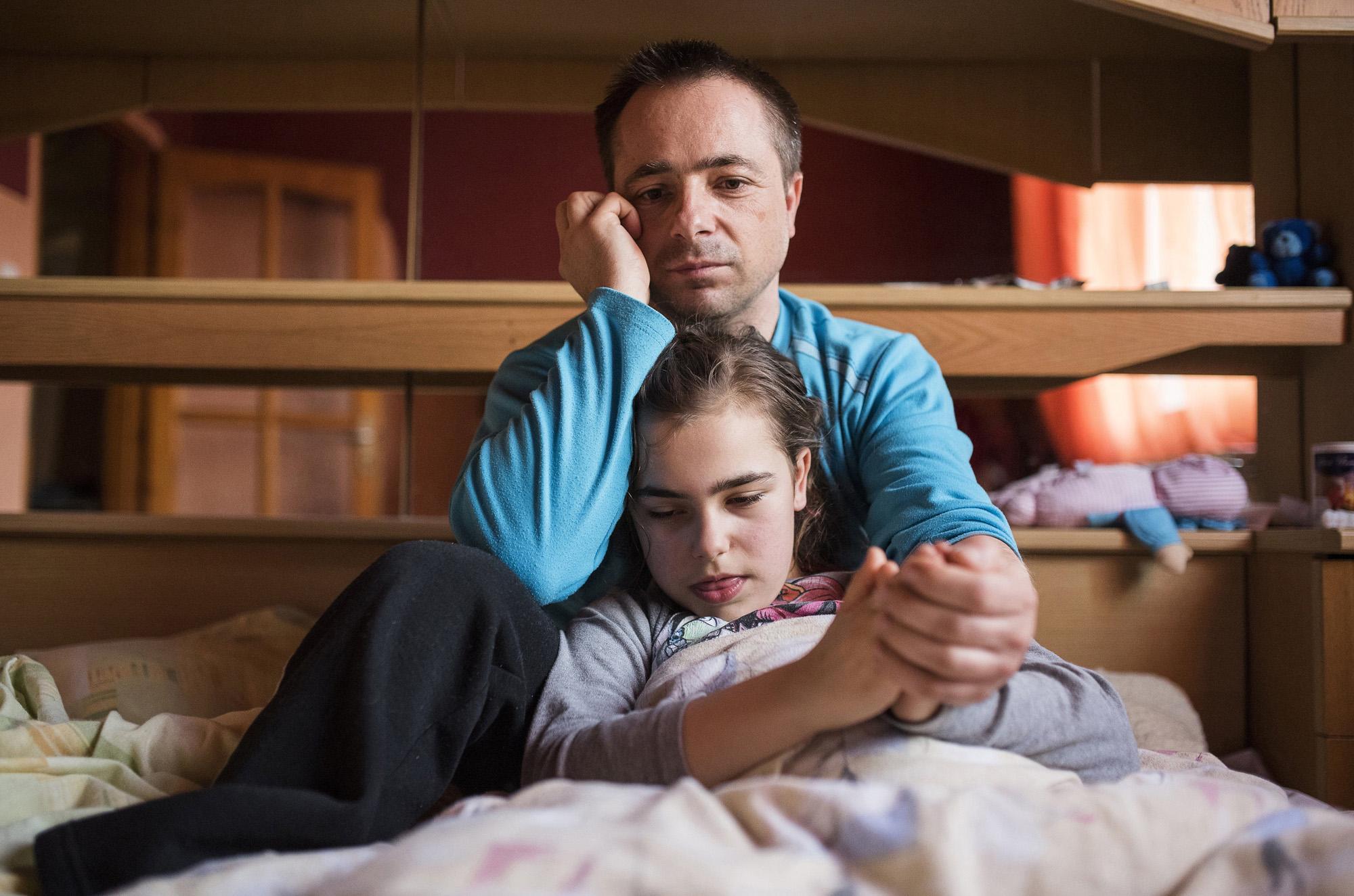 Nyíregyháza, 2017. március 30.Farkas Árpád ül autizmus spektrumzavarral élő, aznap rohamoktól szenvedő lánya, Farkas Laura mellett nyíregyházi otthonukban 2017. március 23-án. Az állandó felügyeletet igénylő gyermek nevelésének nehézségei miatt a család felbomlott, a szülők elváltak. A két gyermekét egyedül nevelő Farkas Árpád korábban jól működő vállalkozásaira nem tudott elég időt fordítani, így az egykor jó körülmények között élő család anyagi helyzete megváltozott. A férfi alapító elnöke az autista gyerekek szülői szervezetének, a 2014 tavaszán bejegyzett Most Élsz Egyesületnek, amely folyamatosan keresi a gyógyítás újabb és újabb lehetőségeit.MTI Fotó: Balázs Attila