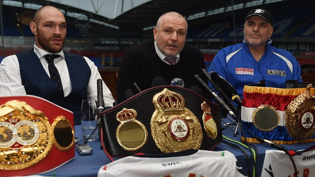 Britain's world heavyweight champion Tyson Fury (L) and John Fury (R) listen as trainer and uncle Peter Fury talks during a press conference in Bolton, north west England on November 30, 2015. Tyson Fury was crowned the new world heavyweight champion on November 28, ending Wladimir Klitschko's nine-year reign as champion in 12 rounds. AFP PHOTO/PAUL ELLIS / AFP PHOTO / PAUL ELLIS