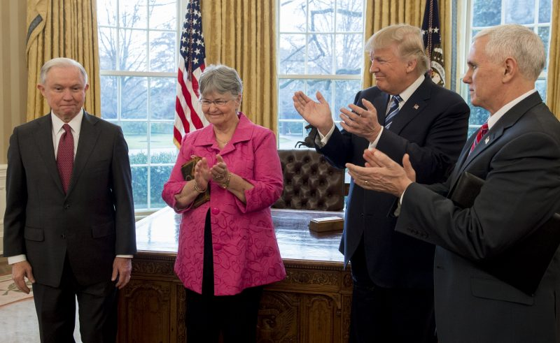 US President Donald Trump applauds Jeff Sessions (L), alongside his wife Mary (2nd L), after he was sworn in as Attorney General by US Vice President Mike Pence (R) in the Oval Office of the White House in Washington, DC, February 9, 2017. / AFP PHOTO / SAUL LOEB