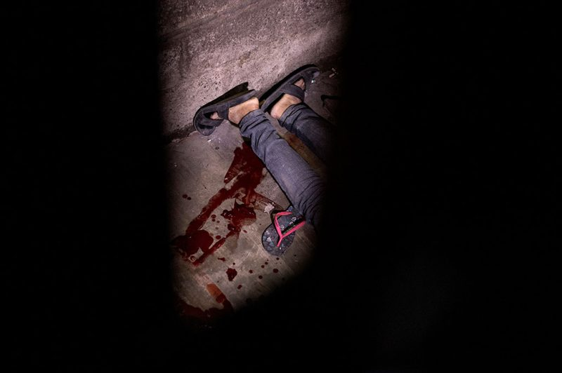 This picture taken on February 16, 2017 shows the dead body of a suspected drug dealer on the ground inside a house after unidentified assailants gunned him down at an informal settlers community in Manila.Shadowy assassins have killed scores of poor victims in the Philippines after President Rodrigo Duterte officially ordered police to withdraw from his deadly drug war, a rights monitor said on February 17. / AFP PHOTO / NOEL CELIS