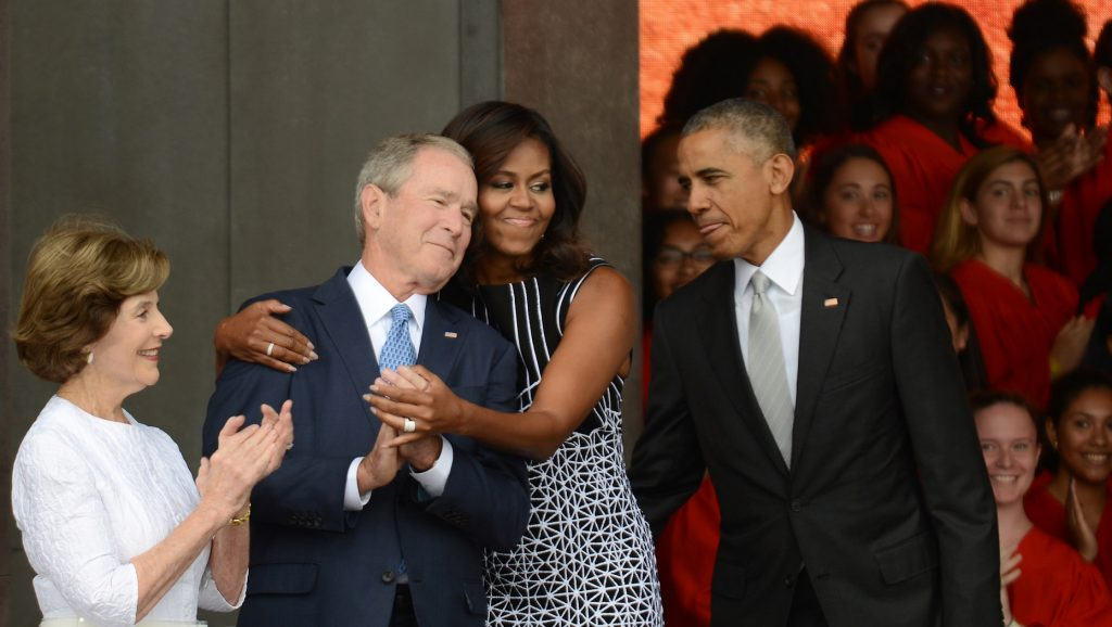 WASHINGTON, DC - SEPTEMBER 24: President Barack Obama watches first lady Michelle Obama embracing former president George Bush, accompanied by his wife, former first lady Laura Bush, while participating in the dedication of the National Museum of African American History and Culture September 24, 2016 in Washington, DC, before the museum opens to the public later that day. The museum is a Smithsonian Institution museum located on the National Mall featuring African American history and culture in the US.   Astrid Riecken/Getty Images/AFP