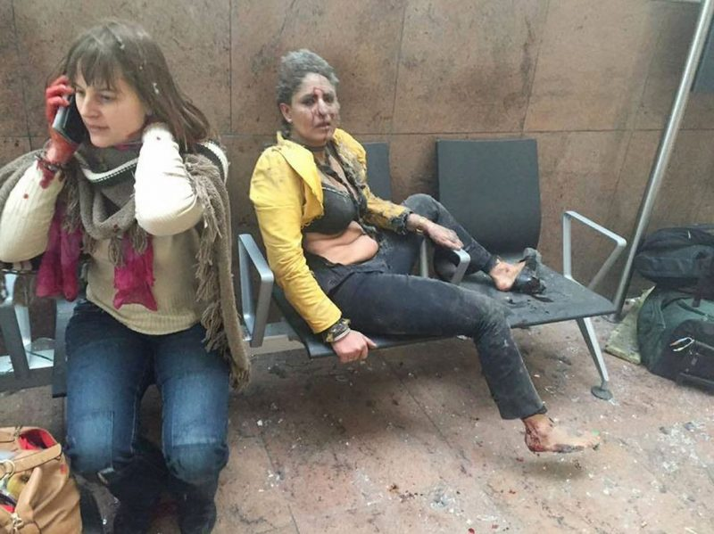 """An injured woman looks on as another speaks on her mobile phone following twin blasts at Brussels airport in Zaventem on March 22, 2016 as part of co-ordinated attacks claimed by Islamic State group (IS) millitants at the city's airport and in a Metro train.Airlines cancelled hundreds of flights and European railways froze links with Brussels  after a series of bombs blasts killed around 35 people in the city's airport and a metro train, sparking a broad security response. Belgium locked down the capital, home to the headquarters of the European Union and NATO, and imposed its highest level of security alert after the explosions, which extinguished about 20 lives in the metro and another 14 in the airport, according to authorities in Brussels. / AFP PHOTO / Georgian Public Broadcaster / Ketevan Kardava / RESTRICTED TO EDITORIAL USE - MANDATORY CREDIT """"AFP PHOTO / KETEVAN KARDAVA / Georgian Public Broadcaster"""