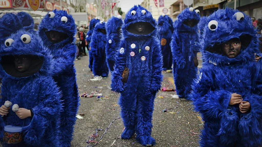 """Revelers dressed as Sidney, the cookie monster, participate in the annual carnival parade in Torres Vedras on February 9, 2016. The Torres Vedras Carnival is allegedly the """"most Portuguese"""" of all the carnivals in the country recognized by the strong political and football satire of the revelers disguises and their floats.  / AFP PHOTO / PATRICIA DE MELO MOREIRA"""