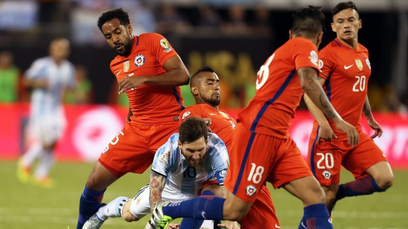 Argentina's Lionel Messi(C) is tackled down by players of Chile during the 2016 Copa America Centenario soccer tournament Final at the Metlife Stadium in New Jersey, the United States on June 26, 2016. Chile defeated Argentina with 4-2 in penalty shootout.