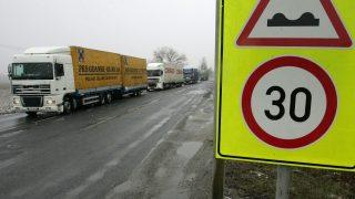 Rédics, 2009. február 25. Kamionok haladnak el egy sebességkorlátozó tábla mellett a 86-os fõúton Rédics közelében. A Nyugat-Dunántúl egyik legforgalmasabb fõútjának számító 86-os fõúton egyes helyeken összefüggõ kátyúk borítják az útburkolatot, ezért a közútkezelõ sebességkorlátozó táblákat helyezett ki, egyes szakaszokon 90 km/h helyett csak 30 km/h-val lehet közlekedni. MTI Fotó: Varga György