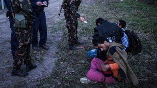 Röszke, 2015. szeptember 15.Katonák és rendőrök három elfogott illegális bevándorlót őriznek a biztonsági határzár mellett a szerb-magyar határon, Röszke térségében 2015. szeptember 15-én. Szeptember 15-én hatályba léptek a migrációs helyzet miatti új szabályozások.MTI Fotó: Ujvári Sándor
