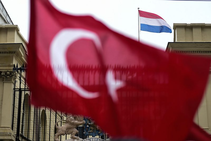 """This picture taken on March 12, 2017, shows a Turkish national flag waved in front of the Dutch Consulate in Istanbul.Protestors briefly took down the Dutch flag at the Dutch consulate in Istanbul and replaced it with a Turkish one, AFP journalists saw, as tensions escalated in a diplomatic row. Turkey's Family Minister Fatma Betul Sayan Kaya was back in Istanbul after being expelled from the Netherlands and escorted back to Germany by Dutch police, condemning The Hague's """"ugly"""" treatment. / AFP PHOTO / YASIN AKGUL"""