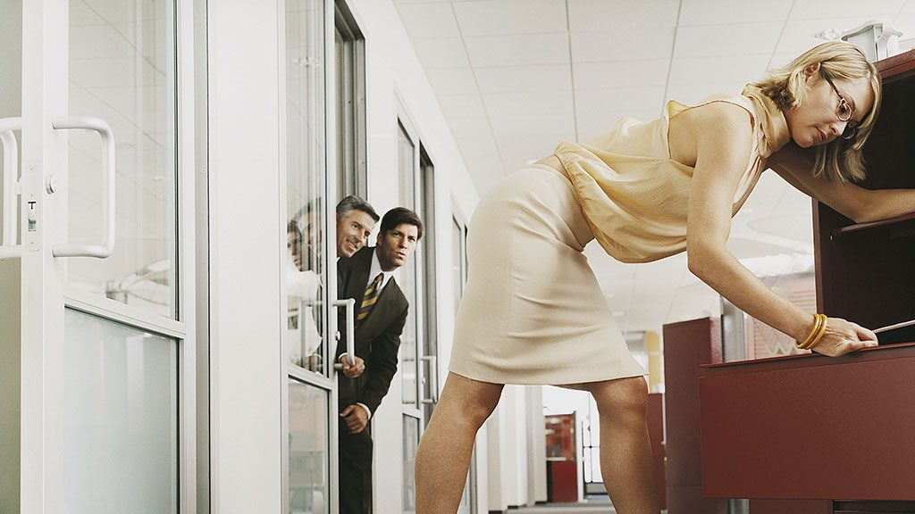 Businessmen Looking Around an Office Door Staring at a Businesswoman Searching in a Filing Cabinet